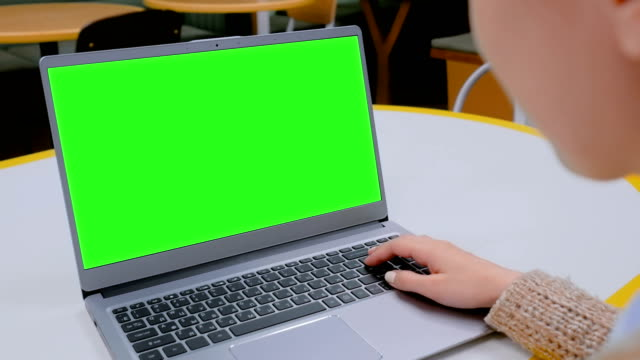 Woman looking at laptop computer with blank green screen in cafe