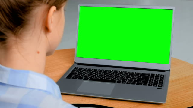 Woman looking at laptop with empty green display