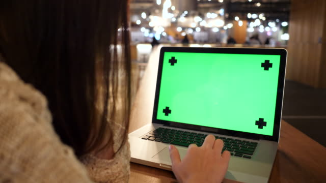 Woman looking at laptop with green screen