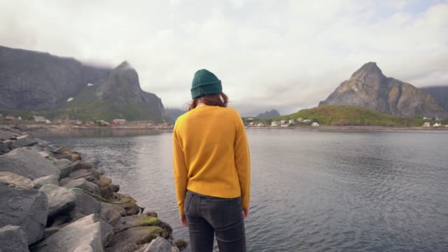 Woman looking at Reine village in Lofoten Islands