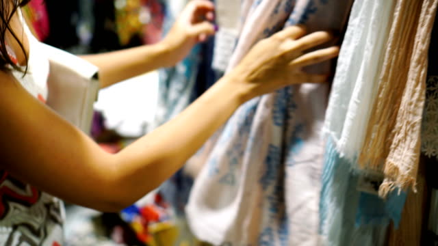 woman looking at scarf in clothing store - copricapo abbigliamento video stock e b–roll