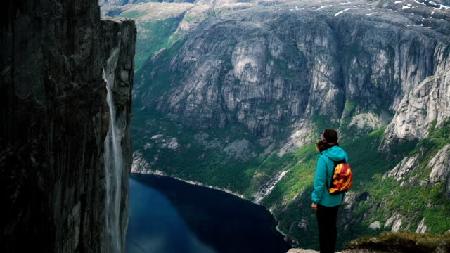 woman looking at scenic view of lysefjorden from kjerag mountain - fiordo video stock e b–roll