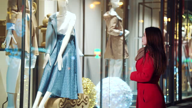 Woman looking at showcase of fashion store video
