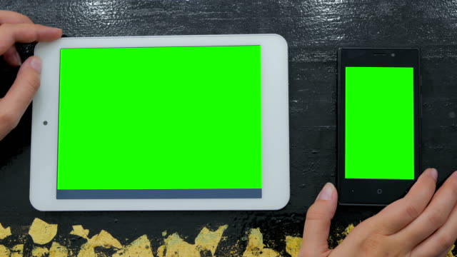 Woman looking at smartphone and digital tablet with green screen video