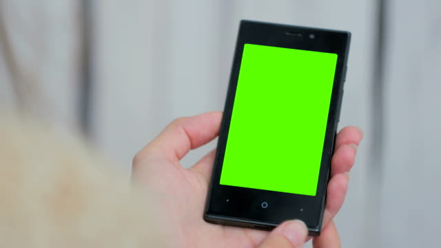 Woman looking at smartphone with green screen video
