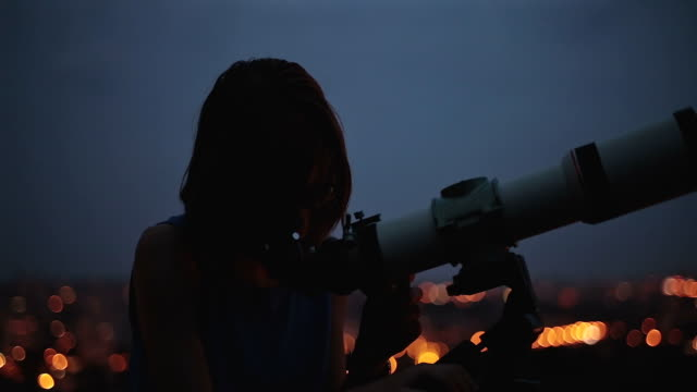 woman looking at the stars through a telescope. - astronomia video stock e b–roll