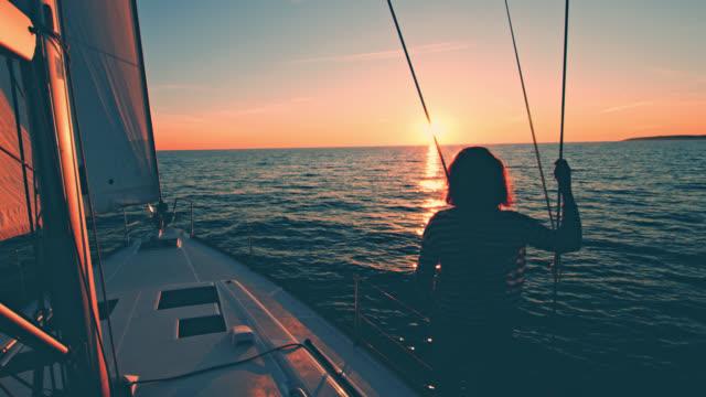 WS mulher olhando o pôr do sol em um veleiro de regata - vídeo