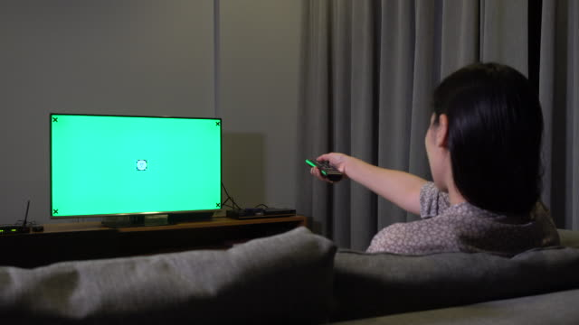 Woman Looking at TV with Green screen at Night