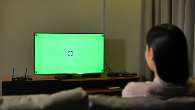 Woman Looking at TV with Green screen at Night Woman Looking at TV with Green screen at Night watching tv stock videos & royalty-free footage