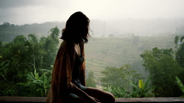 woman looking at  view of jungles under the rain  in bali - индонезия стоковые видео и кадры b-roll
