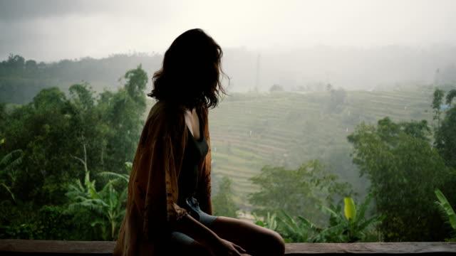 ormanlarda bali yağmur altında görünümünü bakarak kadın - turistik yer stok videoları ve detay görüntü çekimi