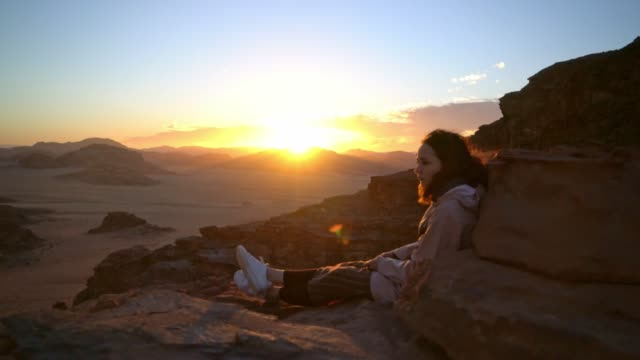 woman looking at  wadi rum desert from rock - rock formations stock videos & royalty-free footage