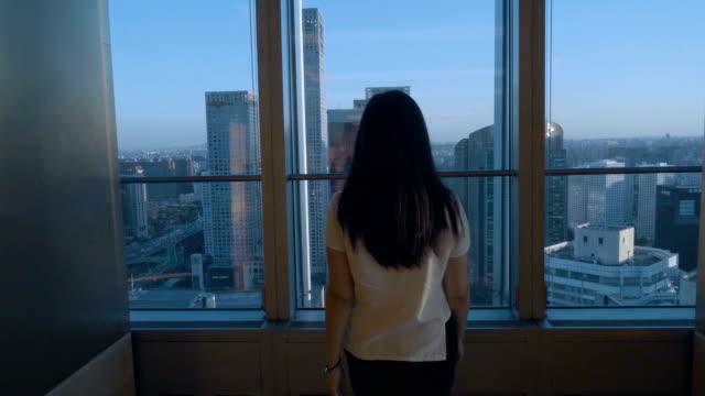 kvinna som tittar stadsbilden i office - titta på utsikt bildbanksvideor och videomaterial från bakom kulisserna
