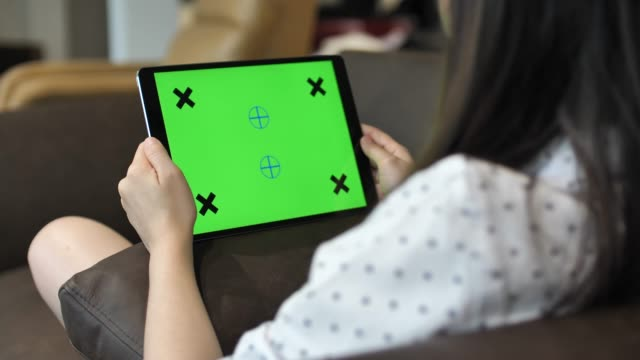 woman looking digital tablet with green screen, horizontal - ipad video stock e b–roll