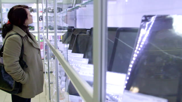 Woman looking for new gadget in electronics store