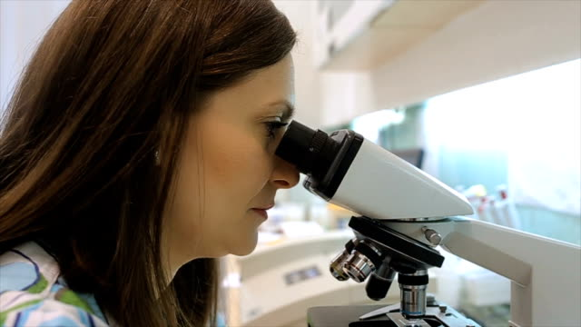 woman looking in a microscope in a modern laboratory video