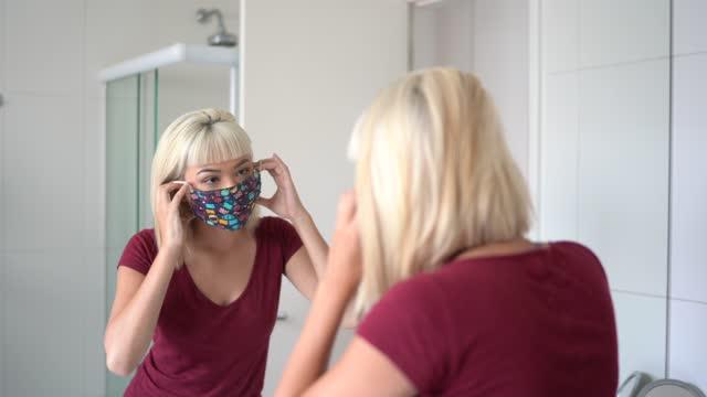 stockvideo's en b-roll-footage met vrouw die in de spiegel kijkt en gezichtsmasker thuis zet - mirror mask