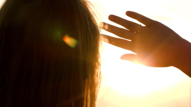 woman looking into distance hiding from the sun - vidbild bildbanksvideor och videomaterial från bakom kulisserna