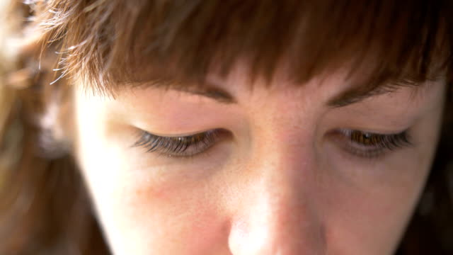 vídeos de stock e filmes b-roll de woman looking into the camera and wears contact lenses close-up - contacts