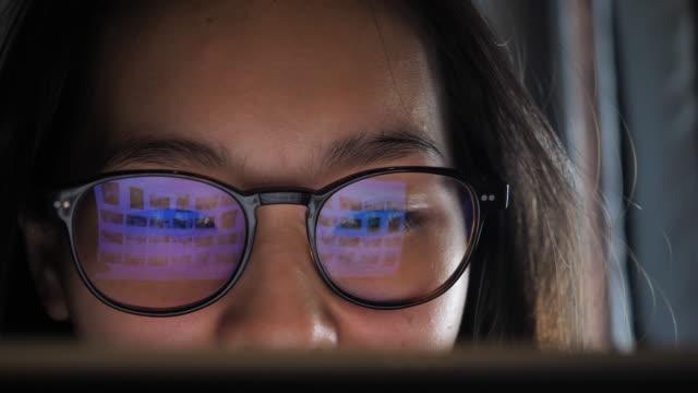 woman looking on computer, refection on eye glasses - odbicie zjawisko świetlne filmów i materiałów b-roll