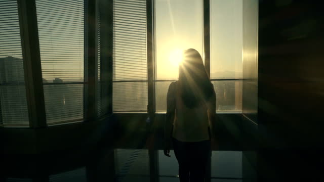 Woman looking out in office with sunset video