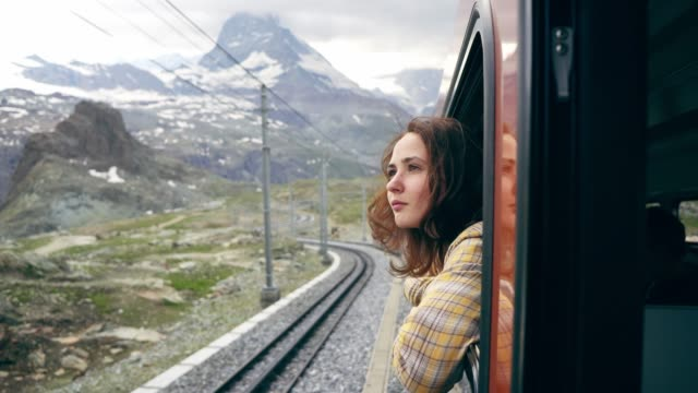 woman looking out of the window on the train near matterhorn - turystyka filmów i materiałów b-roll