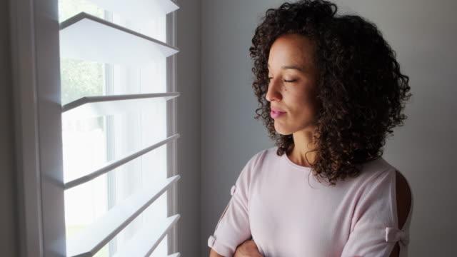 kvinna tittar ut genom fönstret - endast en ung kvinna bildbanksvideor och videomaterial från bakom kulisserna
