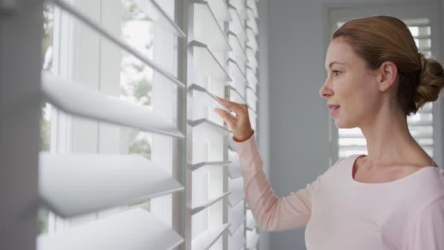 kobieta patrząc na zewnątrz przez okno w wygodnym domu 4k - store filmów i materiałów b-roll