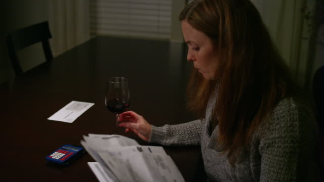 A woman looking over bills at the table, looking stressed and drinking wine video