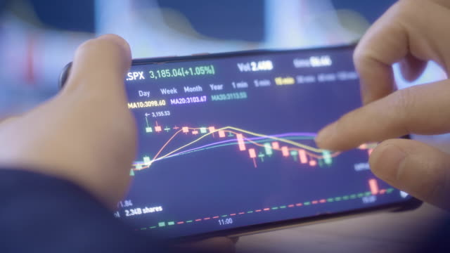 woman looking stock market data on smart phone - azionare video stock e b–roll