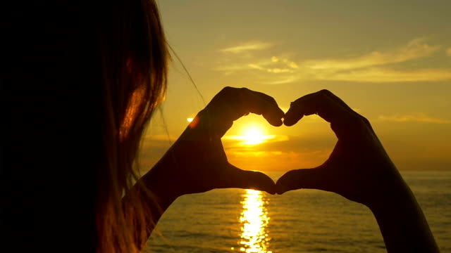 SLOW MOTION: Woman looking the golden sunset through heart hands video