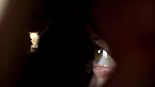 a woman looking through a hole - donna si nasconde video stock e b–roll