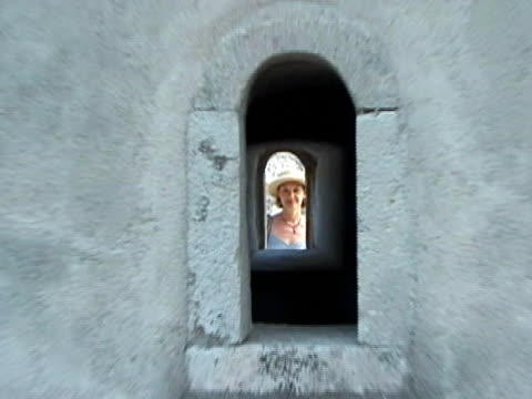 Woman Looking Through Castle Window, Push Woman Looking Through Castle Window, Push.  SD 4:3 NTSC 720 x 486i @ 29.97 fps. Motion-B Compression. Natural background audio. (SD025).    See similar video clips at http://www.istockphoto.com/korudirect.   one mid adult woman only stock videos & royalty-free footage