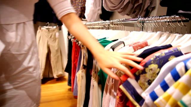 vídeos de stock, filmes e b-roll de mulher olhando através de camisas em uma loja - boutique