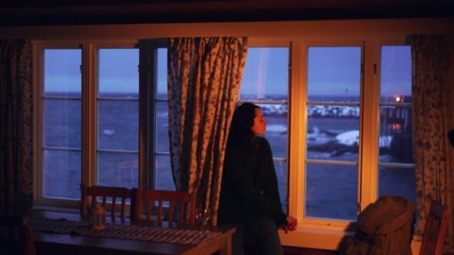 Woman looking through window from cabin  on Lofoten islands in winter