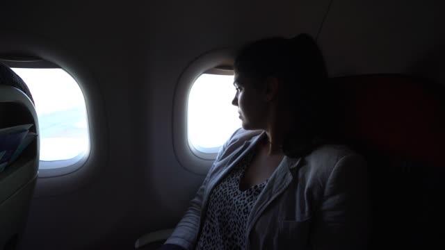 stockvideo's en b-roll-footage met vrouw kijkt door raam op vliegtuig - raam bezoek