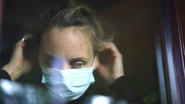 stockvideo's en b-roll-footage met de vrouw die door venster kijkt zet op gezichtsmasker - ongerustheid