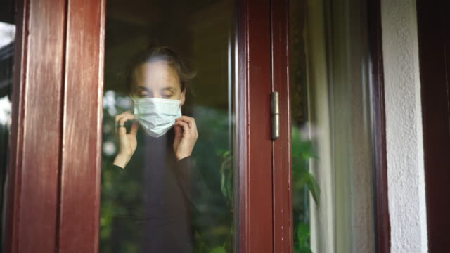 Woman looking through window puts on face mask