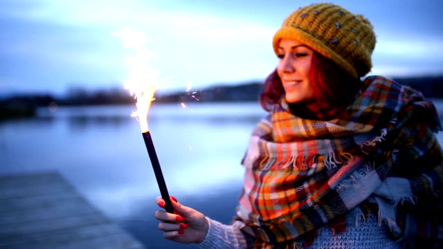 Woman looking to the lake,holding sparkles video