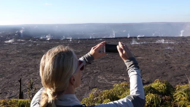 woman looks across volcanic landscape, takes smart phone pic - riserva naturale parco nazionale video stock e b–roll