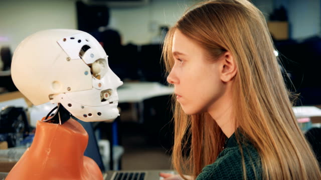Woman looks at a robot's face. Human and robot. Female engineer looks at a droid. cyborg stock videos & royalty-free footage