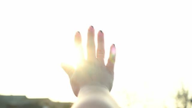 女性は手を通して明るい太陽を見る。太陽の魔法の光が指を通して輝きます。 - 指点の映像素材/bロール