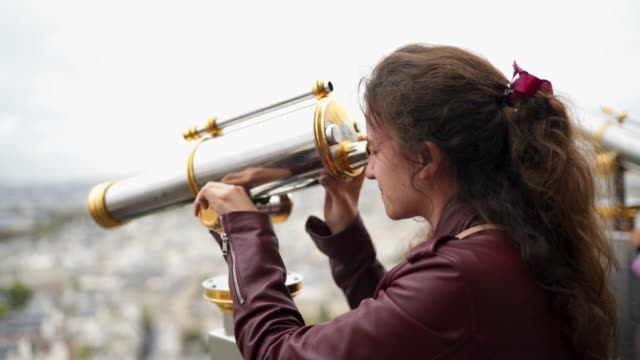 A woman looks into the Eiffel Tower telescope