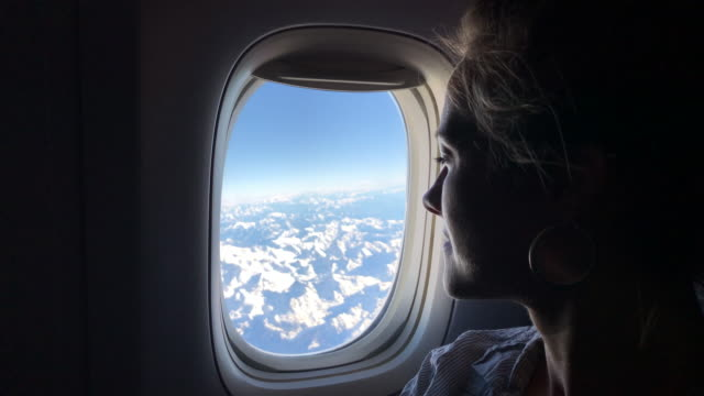Woman looks out of airplane window over alps Blue sky and snowy mountains plane stock videos & royalty-free footage