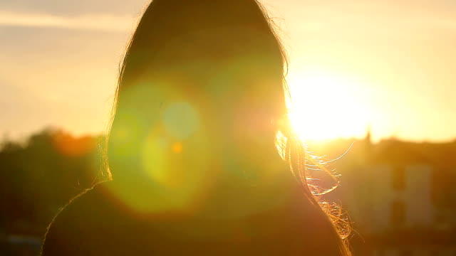 woman looks the sunset: slow motion footage