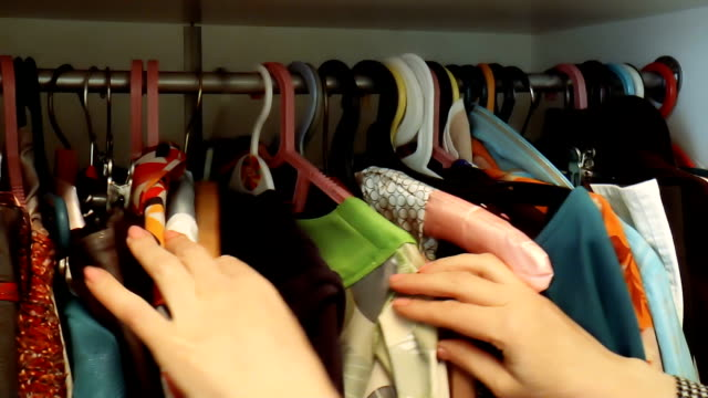 vídeos y material grabado en eventos de stock de mujer busca a través de vestidos y camisas en el armario - abrigo