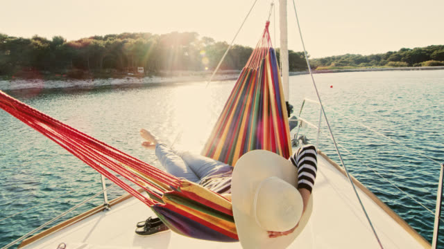 SLO MO Woman lying in a hammock on a sailboat Slow motion wide shot of a woman with a sunhat lying in a hammock on a sailboat deck. Shot was taken in the late afternoon sun. Shoot in 8K resolution. holiday stock videos & royalty-free footage