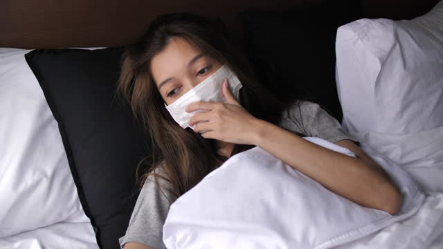 Woman Lying In Bed Suffering With Cold