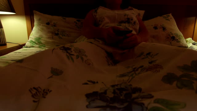 Woman lying in bed watching TV at night video