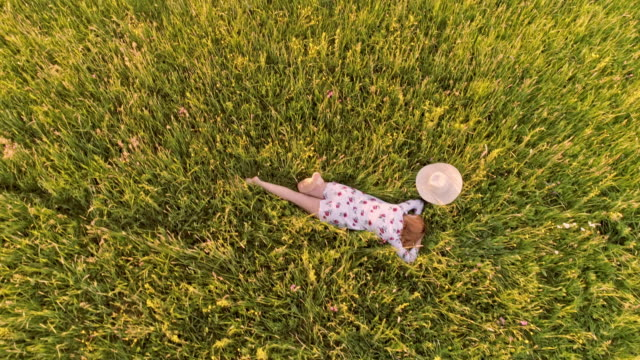 AERIAL Woman lying in grass in the countryside video